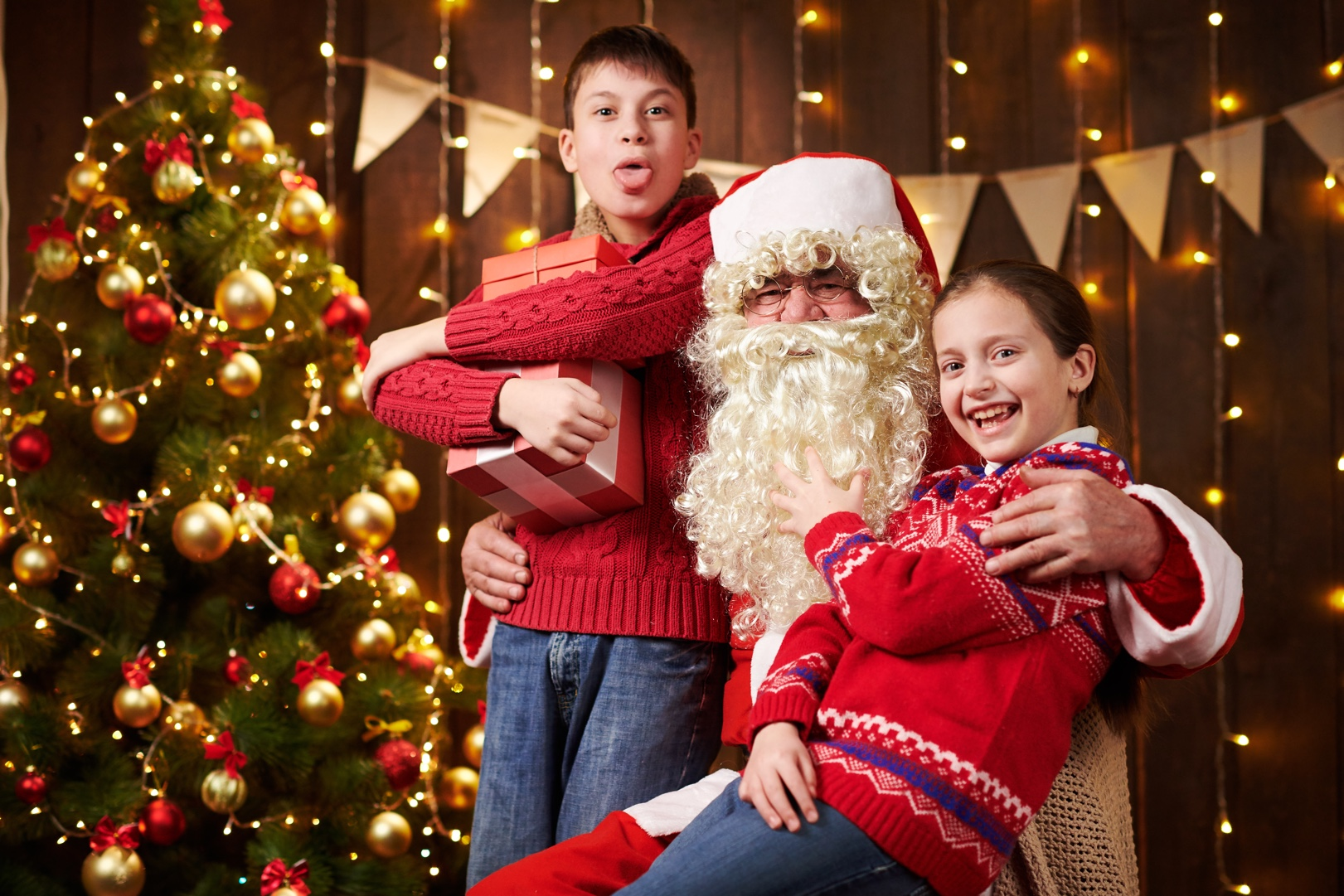 Santa Claus and child boy and girl posing together indoor near decorated xmas tree with lights, they talking, smiling and accepting gifts - Merry Christmas and Happy Holidays!
